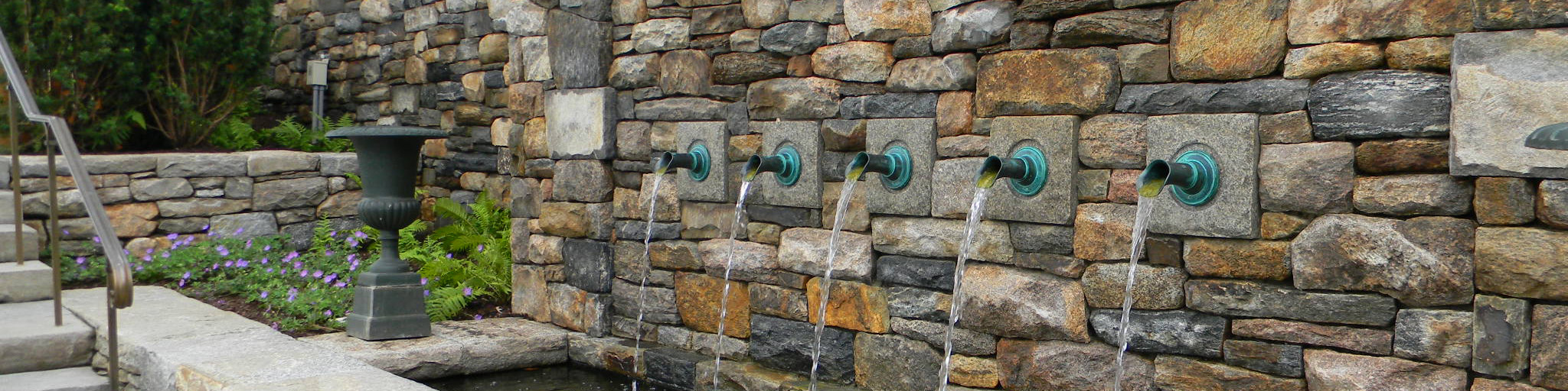 Decoarative fountain with bronze spouts on stone wall